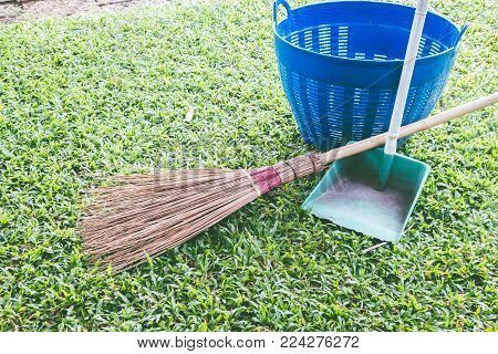 Set of street cleaning - broom and dustpan on green grass