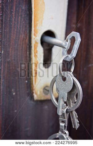 Keychained set of metal keys standing still in an old rustic lock, attached to wooden door