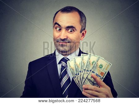 Funny sly business man holding looking at money