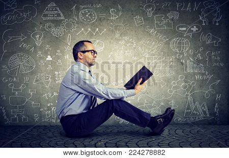 Man in glasses reading a book on a background with science formulas
