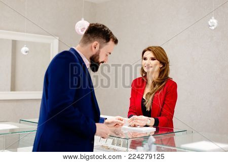 Man Choosing Engagement Ring In Jewelry Ring.