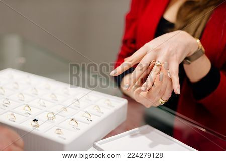 Female seller in a luxury jewelry store presents a ring. Buying a engagement ring. Jewelry store. Woman jeweler.