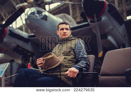 A man sitting on a chair with plane against him.