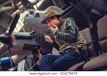 A man in a hat smoking cigarette against old airplane.