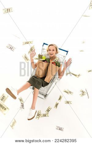 excited young woman with grocery bags sitting in shopping trolley and throwing dollar banknotes isolated on white