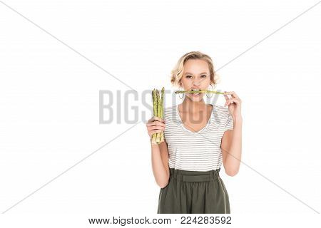 portrait of young woman biting raw asparagus in hands isolated on white