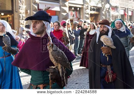 Italy, Florence - January 6 2017: the view of the men in medieval costume holding predatory birds at traditional parade of Epiphany Befana, medieval festival in Florence on 6 January 2017, Florence, Tuscany, Italy.