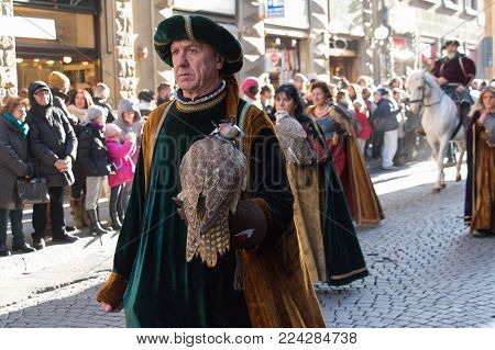 Italy, Florence - January 6 2017: the view of the man in medieval costume holding predatory bird at traditional parade of Epiphany Befana, medieval festival in Florence on 6 January 2017, Florence, Tuscany, Italy.