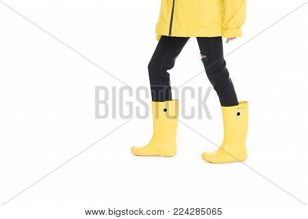 partial view of woman in yellow raincoat and rain boots isolated on white