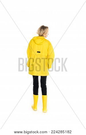rear view of young woman in stylish yellow raincoat and rain boots isolated on white