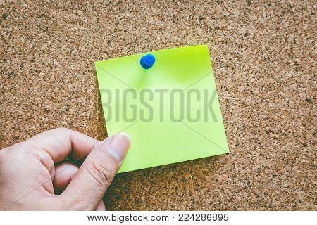 Hand holding reminder sticky note on cork board