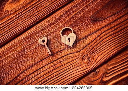 Top view small wooden key to heart and heart-shaped lock on wooden background, Valentine's Day concept