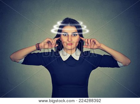 Woman with vertigo closing her ears from noise