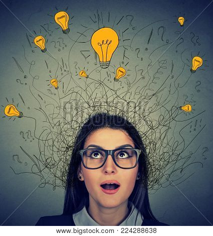 Woman with many ideas light bulbs above head looking up isolated on gray wall background. Eureka concept