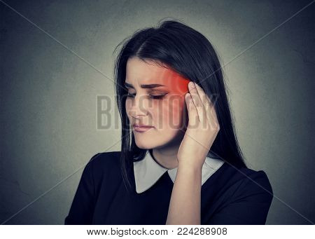 Tinnitus. Closeup up side profile sick female having ear pain touching her painful head temple colored in red isolated on gray wall background