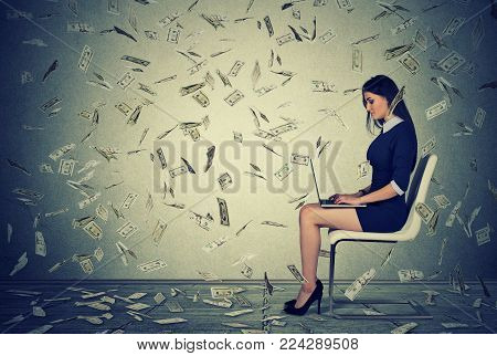Successful young woman using a laptop sitting on a chair building online business making money dollar bills cash falling down. Money rain. Beginner IT entrepreneur success economy concept