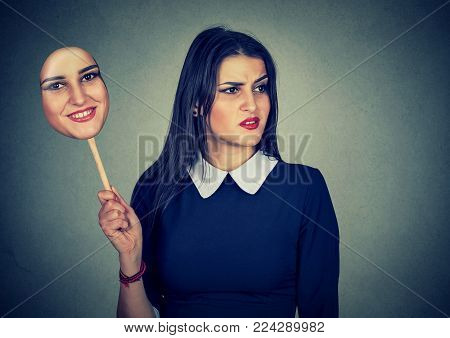 Young woman with disgusted sad expression holding a mask expressing cheerfulness