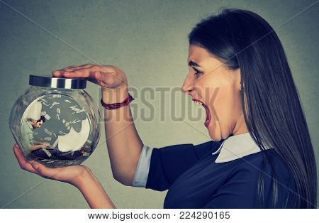 Angry woman holding a glass jar with a young businessman working on laptop under money rain trapped inside