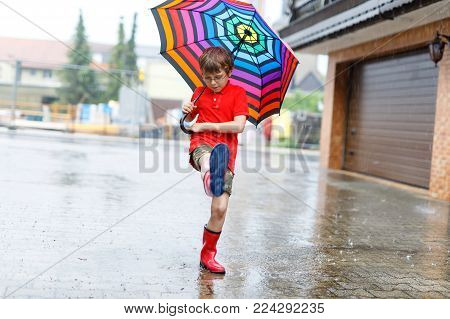 Kid boy wearing red rain boots and walking with colorful umbrella on city street. Child with glasses on summer day. happy kid during heavy summer shower rain