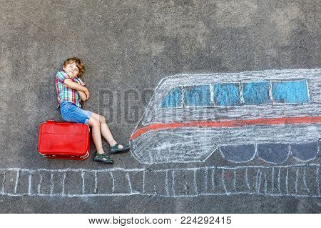 Little kid boy having fun with fast train picture drawing with colorful chalks on asphalt. Child painting with chalk and crayon and going on vacations. Schoolkid sitting on suitcase. Travel concept