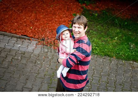 Happy proud young father having fun with newborn baby daughter, family portrait togehter. Dad with baby girl outdoors, love. New born child looking on dad. Bonding, family, new life