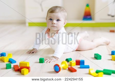 Cute happy smiling baby playing with colorful rattle toys. New born child, little girl learning crawling. Family, new life, childhood, beginning concept. Baby learning grab wooden blocks
