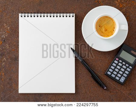 clean white sheet in an open spiral-bound pad, pen, calculator and Cup of coffee on the iron of the rusty metal table, top view