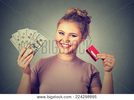 Young woman shopping holding showing credit card and cash dollar banknotes bills
