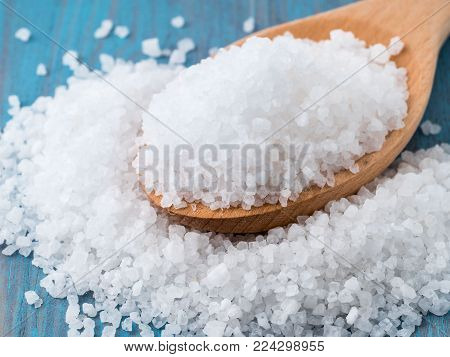 large wooden spoon with big sea salt for the bright blue wooden background, on the table scattered salt crystals, side view