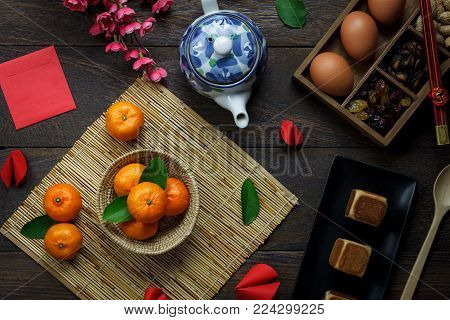 Top view shot of arrangement decoration Chinese new year & lunar holiday background concept.Flat lay orange & dessert also red pocket money on modern brown wooden at home desk.Design for mock up.