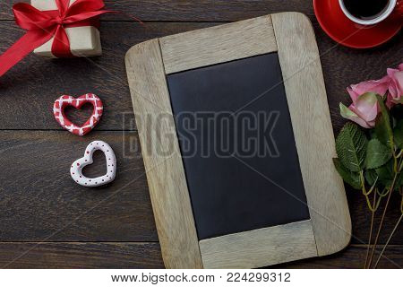 Table top view aerial image of decoration valentine's day background concept.Flat lay arrangement of blank space blackboard & essential items on modern rustic brown wood for mock up creative design