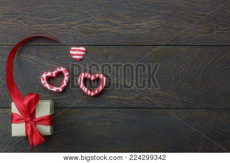 Table top view image of decoration valentine's day background concept.Flat lay heart shape and essential symbol love season with gift box on modern rustic brown wooden at home office desk studio.