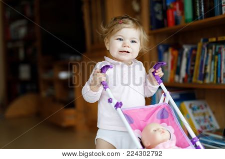 Cute adorable baby girl making first steps with doll carriage. Beautiful toddler child pushing stroller with toy at home. Happy daughter.