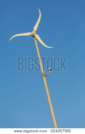 Low angle view of single windmill with blue sky