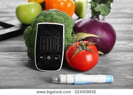 Digital glucometer, lancet pen and vegetables on table. Diabetes diet
