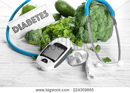 Digital glucometer, lancet pen, stethoscope and vegetables on table. Diabetes diet