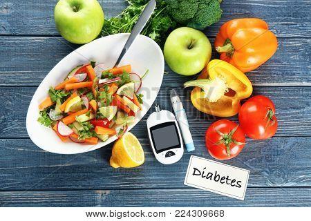 Digital glucometer, lancet pen and bowl of salad on table. Diabetes diet