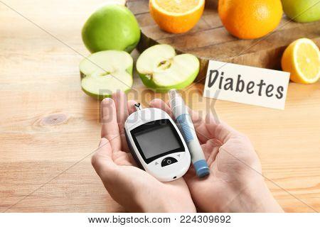 Woman holding digital glucometer and lancet pen above table. Diabetes diet