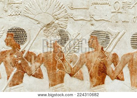 ancient Egyptian wall relief with people figures bringing tools
