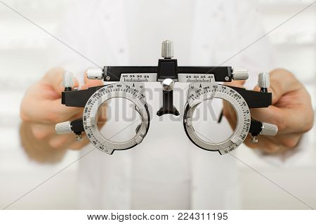 doctor hands holding optometrist trial frame to a patient. Checking vision concept.