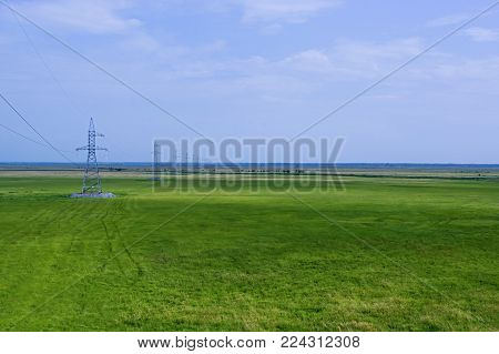 Power line at Prizeyskiy plain, supplies electricity to the city and businesses. Plain overgrown with grass. Grass flattened by the wheels of the car.