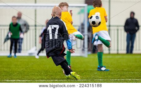 Soccer Football Match. Single Player Kick off. Kids Playing Soccer. Young Boys Kicking Football Ball on the Sports Field. Kids Playing Soccer Tournament Game on the Pitch. Youth European Football Match