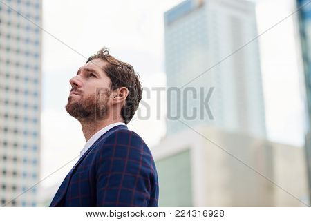 Ambitious young businessman wearing a blazer looking at the office building landscape while standing alone in the city