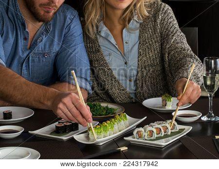 Couple eat sushi rolls on restaurant table. Holding sushi chopstick