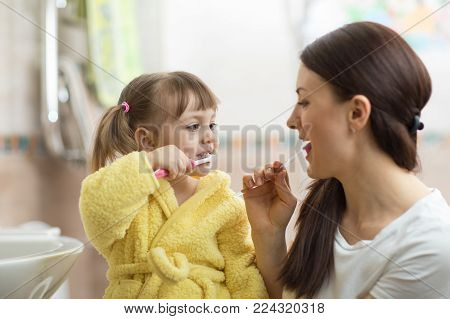 Mother teaches her child daughter teeth brushing