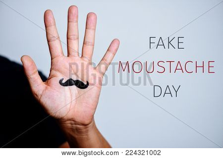 closeup of the palm of a young man with a moustache drawn in it and the text fake moustache day against an off-white background