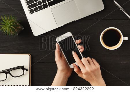 Woman's hands using smartphone with blank screen for advertisement. Top view of human hands, laptop keyboard, coffee, smartphone, glasses, notebook and digital tablet on a wooden table background.