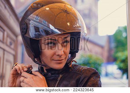 Portrait of cute young woman in a moto helmet.