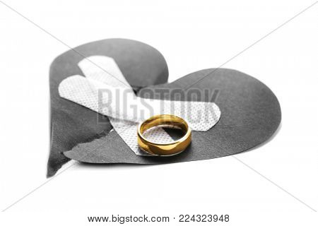 Torn paper heart with medical patches and wedding ring on white background. Relationship problems