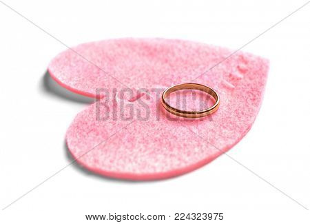 Fabric heart cut in half and sewn back together with wedding ring on white background. Relationship problems